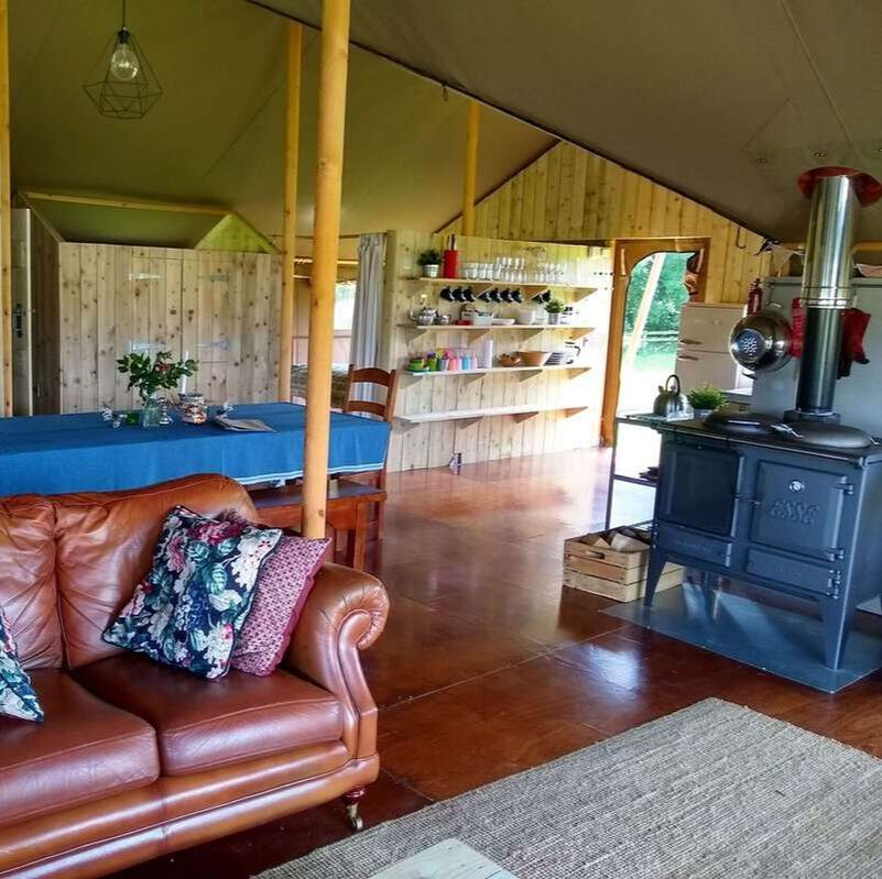 Safari tent interior with wood fire and sofas
